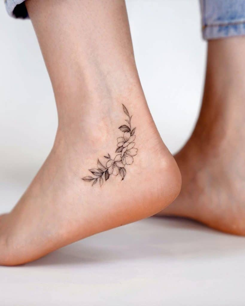 Small Black & White Flower Ankle Tattoo